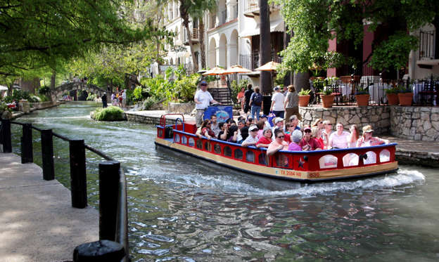 Slide 1 of 16: Patrons take a boat ride next to the San Antonio River Walk