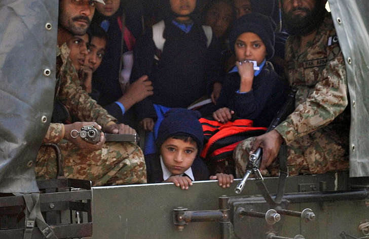 Pakistani soldiers transport rescued school children from the site of an attack