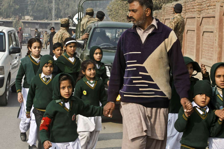 A plainclothes security officer escorts students evacuated from a school as Taliban fighters attack another school nearby in Peshawar, Pakistan, Tuesday, Dec. 16, 2014. Taliban gunmen stormed a military-run school in the northwestern Pakistani city, killing and wounding scores, officials said, in the worst attack to hit the country in over a year.
