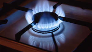 Gas flame coming from burner on stovetop, close-up