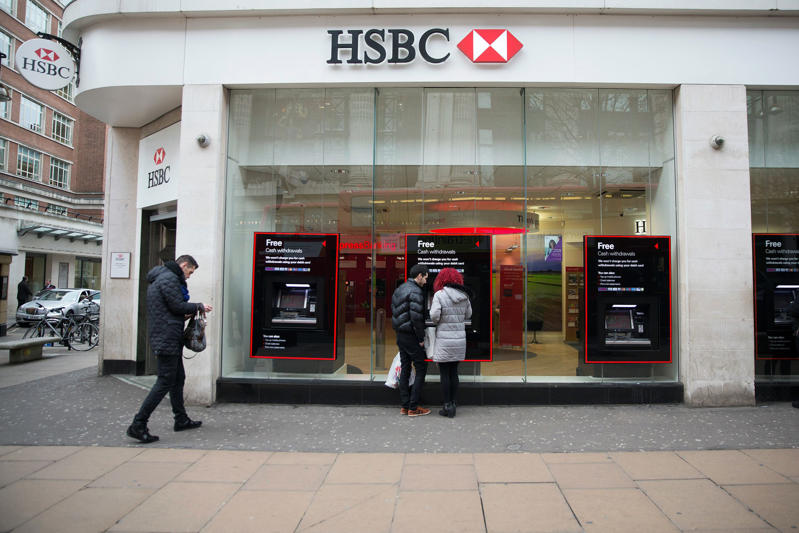 Customers use an HSBC automated teller machine (ATM) outside a bank branch, operated by HSBC Holdings Plc, in London, U.K.,