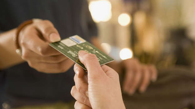 woman handing credit card to cashie