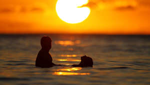 A couple watches the last rays of sunlight for 2011 at sunset from the waters off Waikiki Beach in Honolulu, Hawaii, December 31, 2011. Hawaii is one of the last places on earth that will usher in the New Year.