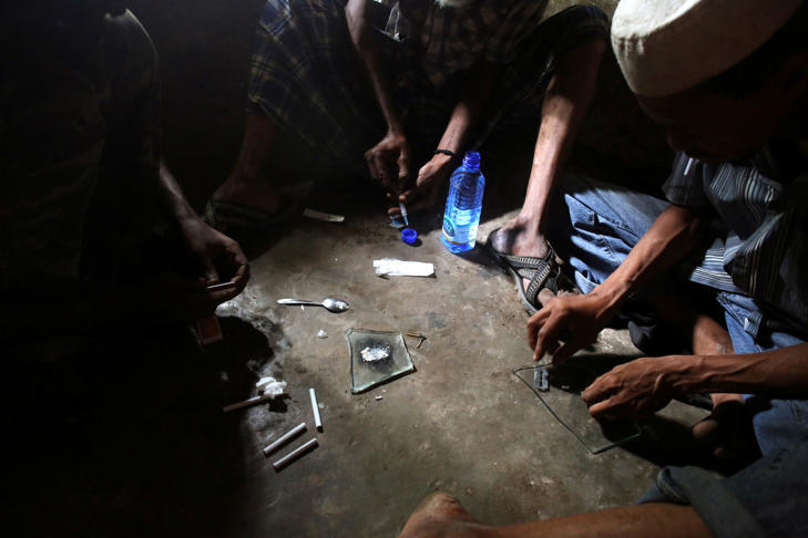 Heroin addicts prepare heroin before using it in Lamu, Kenya, on November 21, 2014.