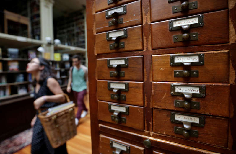 Brown University students Nicha Ratana-Apiromyakij, left, and Nick Melachrinos, walk past a card catalog, right, at the Providence Athenaeum, in Providence, R.I., Monday, July 15, 2013. With roots dating back to 1753, the private library is one of the oldest in the country. It is housed in a Greek Revival-style granite building that neighbors Brown University and the Rhode Island School of Design. (AP Photo/Steven Senne)