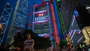 Pedestrians walk near the Bank of China Tower, from left, Cheung Kong Center, Bank of China Building, HSBC Holdings Plc headquarters, Standard Chartered Bank building and Prince's Building stand at night in the Central district of Hong Kong, China