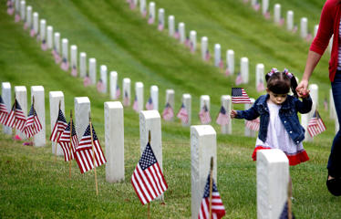 Madelyn Andrews, of Woodland Hills, Calif., walks past military graves while placing flags at headstones in remembrance of Memorial Day, Monday, May 25, 2015, at The Los Angeles National Cemetery in Los Angeles. Richard Vogel/AP